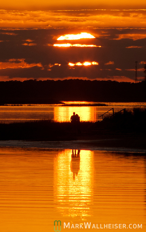A couple watch the sunset at Shell Point in Wakulla County, Florida on the Forgotten Coast south of Tallahassee.