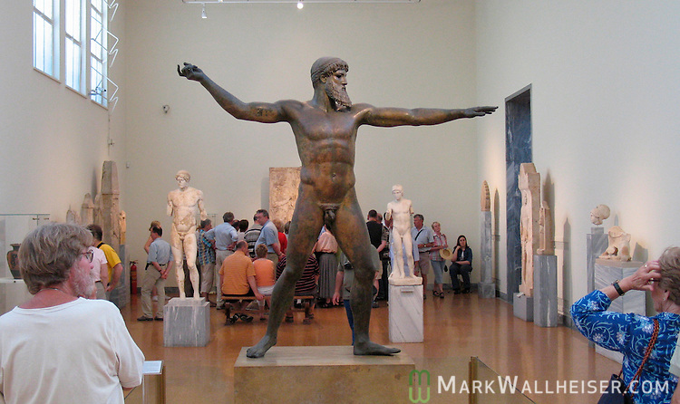 The bronze statue of Poseidon standing in a position to throw his trident.  The statue was created around the 5th century BC and is in a museum in Athens, Greece.