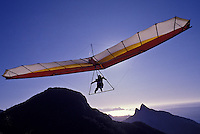 Hang-glider over Tijuca National Park mountains in Rio de Janeiro, Brazil. Sao Sebastiao do Rio de Janeiro, commonly referred to simply as Rio, is the second largest city of Brazil, and the third largest metropolitan area and agglomeration in South America, 6th largest in the Americas, and 26th in the world. It is the most visited city in southern hemisphere and is known for its natural settings. Hang gliding is a popular activity on the nearby Pedra Bonita (Beautiful Rock). After a short flight, gliders land on the Praia do Pepino (Cucumber Beach) in São Conrado. Since 1961, the Tijuca National Park (Parque Nacional da Tijuca), the largest city-surrounded urban forest and the second largest urban forest in the world, has been a National Park.