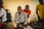 Odong Henry, English and literrature  teacher,  surrounded by his students at Hope North lIbrary, Uganda.