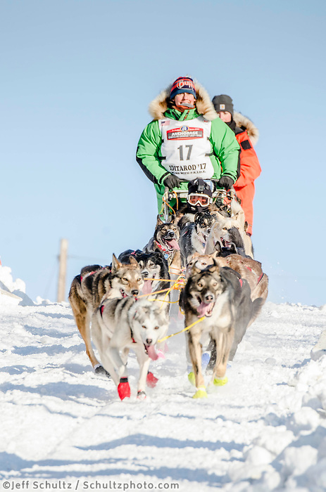 Kristin Bacon and team run past spectators and down the Cordova Street hill with an Iditarider in the basket and a handler during the Anchorage, Alaska ceremonial start on Saturday March 4th during the 2017 Iditarod race. Photo ©2017 by Kristie Lent /SchultzPhoto.com