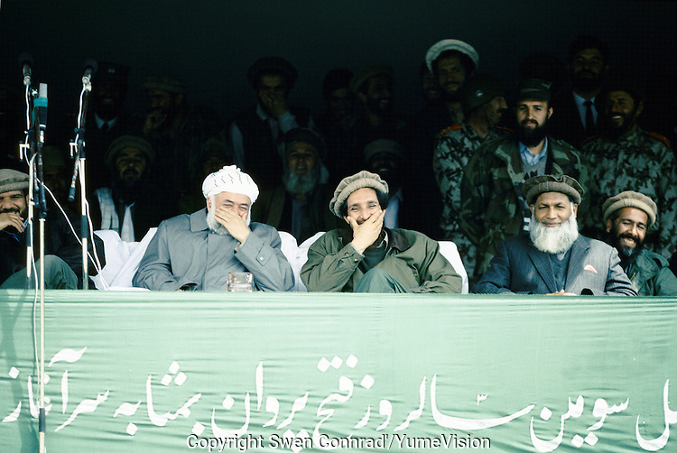 Warlord Ahmad Shah Massoud with President Borhan'udin Rabani, laughing of a Mudjahedin parade, celebrating the liberation of Charikar from the communist army. The General Abdul Quassim Fahim is on the left.
