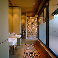 The long bathroom has a pair of matching basins and an open shower that has direct access to the garden via a sliding glass door