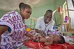 Nurse Elia Ayoub examines 1-year old Mutasim in the pediatric ward of the St. Daniel Comboni Catholic Hospital in Wau, South Sudan. Ayoub is a 2017 graduate of the Catholic Heath Training Institute in Wau. The CHTI is sponsored by Solidarity with South Sudan.<br /> <br /> Hanan Hamed, the boy's mother, looks on. The boy suffers from malaria. The family is displaced by conflict and living in the Protection of Civilians section of the local United Nations base.