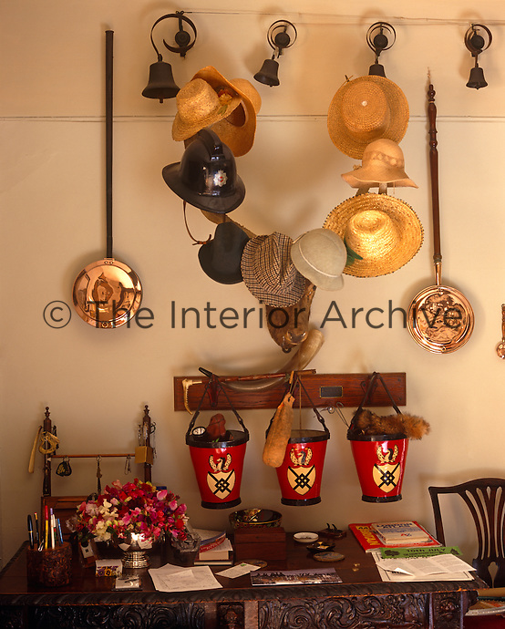 A hall table is cluttered with personal objects and a stag's head used as a hat stand