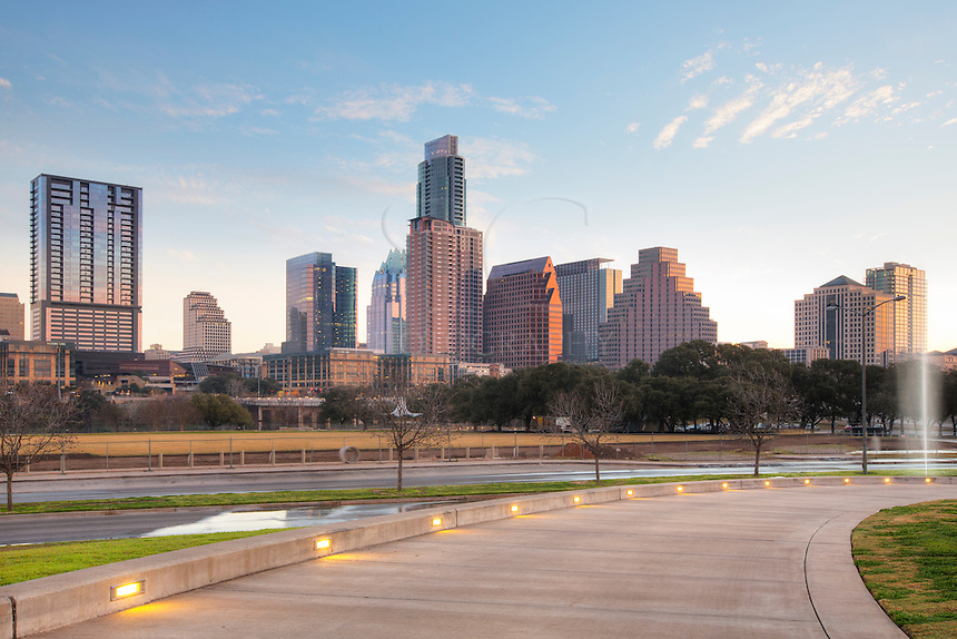 Downtown Austin rises into the February morning as soft light plays across the sky. The skyline, as seen from the walkway wrapping around the Long Center pavillion, features the Austonian, the tallest building in Austin, and the unique architecture of the Frost Tower (partially obscured here). Just scross the street is Zilker Park and Lady Bird Lake and the First Street Bridge.