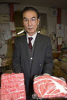 The president of Maiduru corporation, Etsuji Isozaki, holding plastic meat at Maiduru Corporation, Tokyo, Japan, 22nd December 2008. Maiduru corporation makes highly realistic plastic food for display in restaurant and cafe windows. .