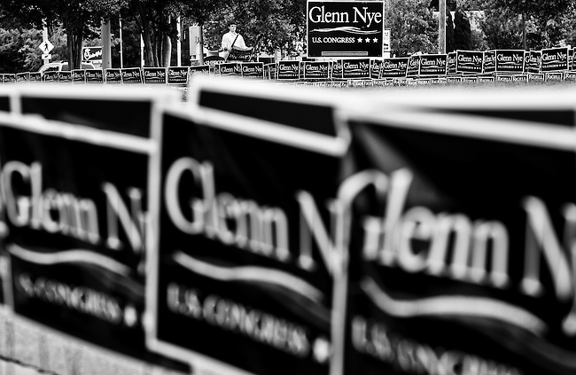 Campaign workers place campaign signs along the street before the debate with U.S. Rep. Glenn Nye, D-Va., Republican challenger Scott Rigell and independent candidate Kenny Golden at Princess Anne High School in Virginia Beach, Va., on Aug. 19, 2010.