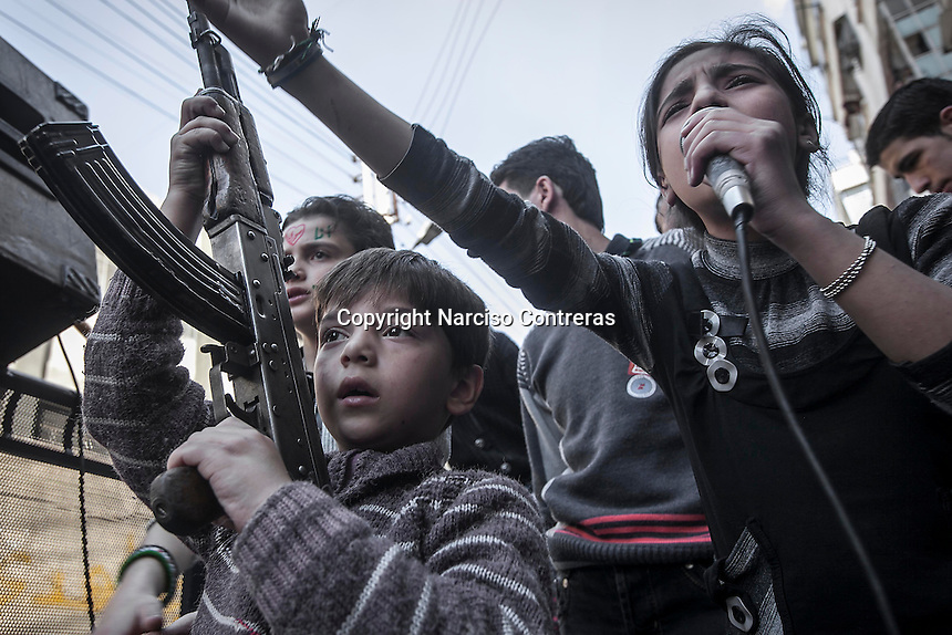A Syrian girl chants anti government songs as a kid holds a weapon during a demostration after preyers in the Bustan Al Qasr district of Aleppo, Syria.