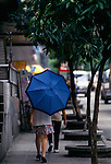 woman pedesrian walking away carries a blue umbrella, sidewalk scene in Guangzhou, China, Asia