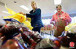 SOUTHBURY CT. 25 November 2013-112513SV01-From left, Kari Anderson of Southbury and Kay Shveda of Southbury help pack bag with other volunteers at the firehouse in Southbury Monday. The Southbury Food Bank was packing 154 Thanksgiving baskets for people in need.<br />  Steven Valenti Republican-American