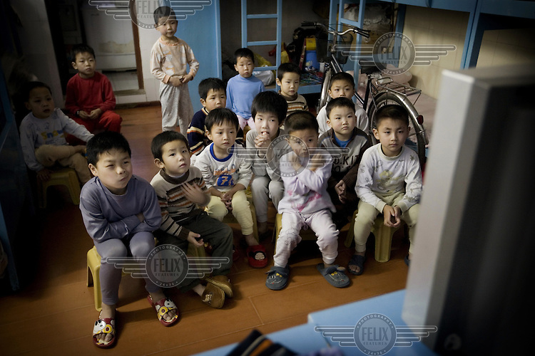Children watch television in the Li Xiaoshuang Gymnastic School in Xiantao. It is an elite school for children with a special talent in gymnastics or acrobatics. The school day consists of a mix of sports and traditional academic studies.