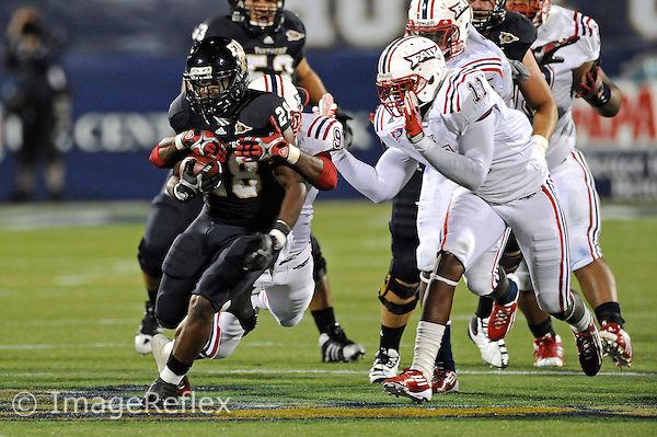 12 November 2011:  FIU running back Darriet Perry (28) attempts to break away from Florida Atlantic linebacker Martin Wright (91) while being pursued by linebacker David Hinds (11) in the third quarter as the FIU Golden Panthers defeated the Florida Atlantic University Owls, 41-7, to win the annual Shula Bowl game, at FIU Stadium in Miami, Florida.