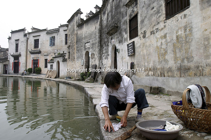 A Chinese woman washion clothes in a pond surrounded by traditional Hui architecture still preserved in the Hongcun Village, a UN World Heritage Site, in Anhui Province, China. China recently hosted a UNESCO world heritage conference, while the country's some 30 listed sites have enjoyed an increase in general public awareness and the resulting tourism, which generates much needed income in China's rural regions while raising concerns from conservation groups over their true preservation..26-JUN-04