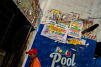 """Champeta music party posters, created by Runner's collective, are seen on the wall in Cartagena, Colombia, 7 December 2018. Hidden in the dark, narrow alleys of Bazurto market, a group of dozen young men gathered around José Corredor (""""Runner""""), the master painter, produce every day hundreds of hand-painted posters. Although the vast majority of the production is designed for a cheap visual promotion of popular Champeta music parties, held every weekend around the city, Runner and his apprentices also create other graphic design artworks, based on brush lettering technique. Using simple brushes and bright paints, the artisanal workshop keeps the traditional sign painting art alive."""