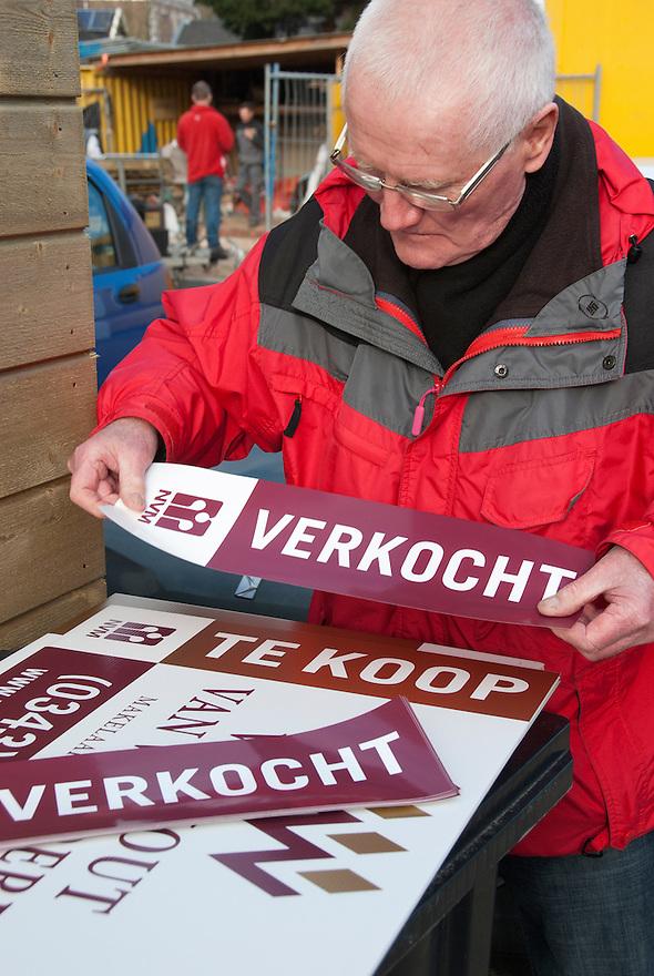 De makelaar plakt het te koop bord over met een verkocht sticker. <br /> (c)renee teunis