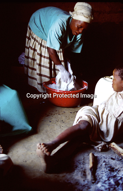 Margarette Shenge, 37, washing clothes on November 28, 1999 in her one room house in Nqbeni, a rural area in Natal, South Africa. She's infected by the Aids virus and has four children. Two of the children are also infected by HIV..(Photo: Per-Anders Pettersson/ Liaison Agency)