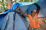 A woman places a new tarp atop her leaky shelter in a camp for more than 5,000 displaced people in Riimenze, in South Sudan's Gbudwe State, what was formerly Western Equatoria. Families here were displaced at the beginning of 2017, as fighting between government soldiers and rebels escalated.<br /> <br /> Two Catholic groups, Caritas Austria and Solidarity with South Sudan, have played key roles in assuring that the displaced families here have food, shelter and water.<br /> The camp formed around the Catholic Church in Riimenze as people fled violence in nearby villages for what they perceived as the safety offered by the church.