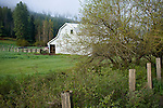 Idaho,Coeur d'Alene. A roadside barn and pasture, with fence in spring.