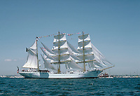 A white, three masted full rigged ship with colorful flags waving in the breeze at the Tall Ships exhibition. Boats, spectator events, sailing. Rhode Island.