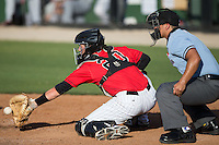 Kannapolis Intimidators catcher Brett Austin (20) reaches for a pitch as home plate umpire Cody Clark looks on during the South Atlantic League game against the Hickory Crawdads at CMC-Northeast Stadium on May 21, 2015 in Kannapolis, North Carolina.  The Intimidators defeated the Crawdads 2-0 in game one of a double-header.  (Brian Westerholt/Four Seam Images)