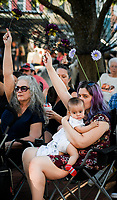 NWA Democrat-Gazette/CHARLIE KAIJO Attendees hold up flowers during a rally, Friday, October 5, 2018 at the town square in Bentonville. Volunteers distributed 51 flowers to honor the 51 women, men and children who lost their lives due to domestic violence last year. <br /><br />A rally was held concerning domestic violence to recognize October as Domestic Violence Awareness Month<br /><br />&quot;Of the 51 people who were killed last year, they came across from all demographics. The youngest was an infant, an unborn child. The eldest was a 74 year old woman. One victim was a nurse. Another was a day care worker, and another was a police officer responding to the domestic violence incident,&quot; said Antonella Kinder, development coordinator for the NWA Women's Shelter. &quot;All of that to say that domestic violence doesn&Otilde;t discriminate.&Oacute;