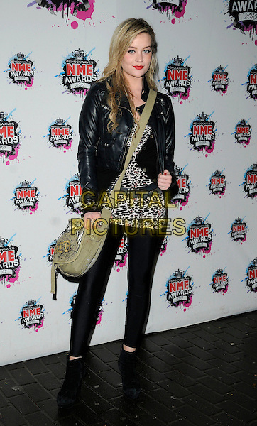 LAURA WHITMORE.The Shockwaves NME Awards 2010 held at Brixton Academy, London, England. .February 24th, 2010.full length black leggings leather jacket ankle boots beige green satchel leopard print top belt white.CAP/CAN.©Can Nguyen/Capital Pictures.
