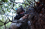 Spc. Justin Kelly, from Sandusky, Mich., prepares to fire at the enemy while concealed behind thick brush on Aug. 2, 2004. As a member of Company B, 5th Battalion, 20th Infantry Regiment, Kelly conducted security operations in support of Operation Sykes Hammer. The operation's objective was to seize weapons and neutralize terrorist activity in Avgone, Iraq. (U.S. Army photo by Sgt. Fred Minnick)