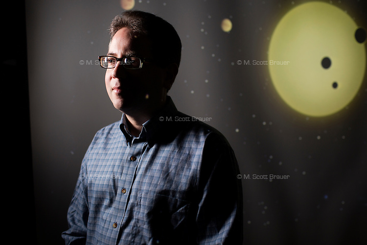 Astrophysicist Dr. Joshua N. Winn is the Class of 1942 Career Development Associate Professor of Physics in the Department of Physics at MIT in Cambridge, Massachusetts, USA.  Winn's research focuses on exoplanetary systems, especially those in which the star and planets eclipse one another. Winn is seen here in front of a projection of an illustration of an exoplanetary system from his research.