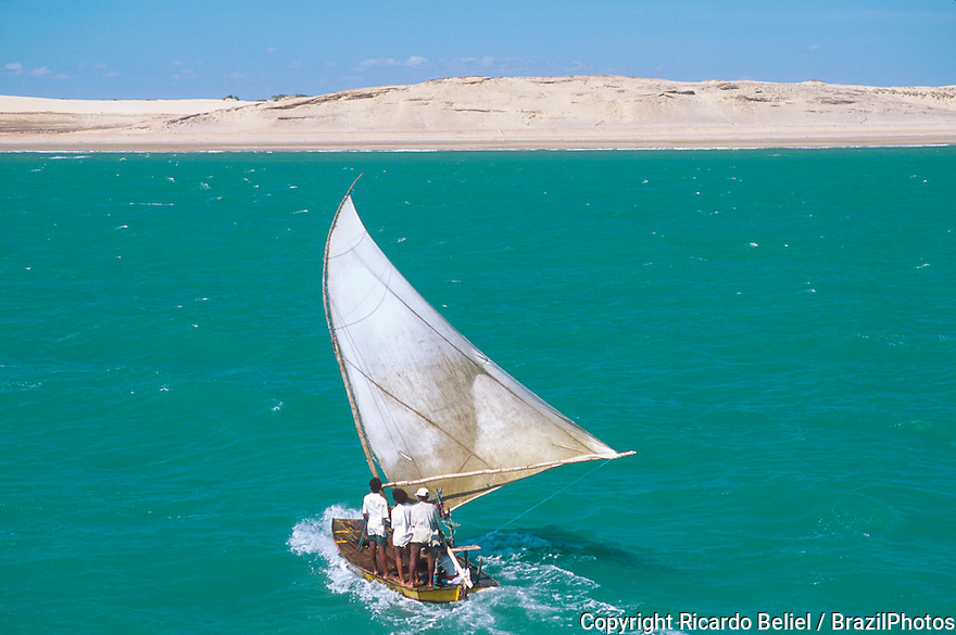 Jangada, seaworth sailing raft used by fishermen of northeastern Brazil, Ceara State shore near Fortaleza, sand dunes in tropical beach.
