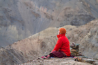 Monk in morning meditation. On the old road  ('Jalebi Mod') near Lamayuru Village,  Ladakh, Jammu and Kashmir, India