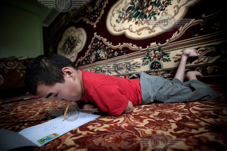 13 year old Anarbek Dolotaliev lies on the floor drawing a picture with a pencil in his mouth. Anarbek has Arthrogryposis, a neuro-musculo-skeletal disorder that affects various joints in the body. It is a congenital disorder that is non-progressive and in this case the condition has been linked to pollution in Mailuu-Suu.....