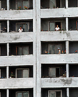 "Residents in an estate, Pyongyang, North Korea. The DPRK (Democratic People's Republic of Korea) is the last great dictatorship where the people are bombarded with images of the ""Eternal President"" Kim Il-sung who died in 1994 and his son and current leader Kim Jong-il who are worshipped like a God."