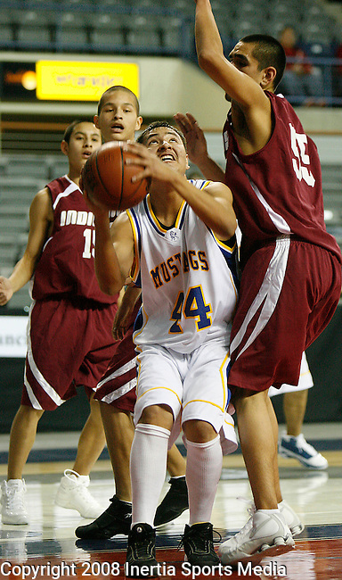 RAPID CITY, SD - DECEMBER 17 :  Daylon Black Bull #44 of Little Wound tries to shoot while being defended upon by Roscoe Grant #55 of Flandreau Indian during their game at the Lakota 32nd Annual Lakota Nation Invitational at the Rushmore Plaza Civic Center Wednesday.