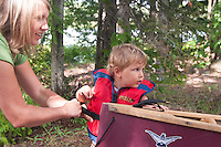 A mother adjusts a lifevest PFD on her young son while getting ready to canoe at Craig Lake State Park near Michigamme Michigan.