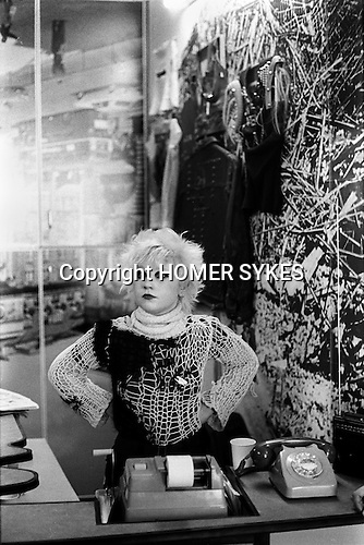 1970s fashion interior of the Malcolm McLaren and Vivienne Westwood shop called Seditionaries at 430 Kings Road Chelsea. 1977. The shop assistant is Debbie Wilson (aka Debbie Juvenile) one of the coterie of early Sex Pistol fans known as the Bromley Contingent. She appeared in The Great Rock and Roll Swindle.She is wearing a Hangman Jumper.