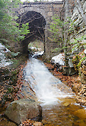 Stone bridge along the old Maine Central Railroad in Harts Location, New Hampshire USA during the spring months. This bridge crosses Kedron Brook. Since 1995 the Conway Scenic Railroad, which provides passenger excursion trains has been using the track.