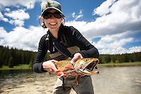 An angler holds a brook trout at a mountain lake in Yellowstone National Park.