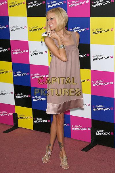 JENNA JAMESON.Attending the T-Mobile Sidekick iD Launch, .held at the T-Mobile Sidekick Lot,  Los Angeles, California, USA,13 April 2007..full length pinafore lilac beige dress smock profile holding white mobile cell phone tattoos.CAP/ADM/ZL.©Zach Lipp/AdMedia/Capital Pictures.