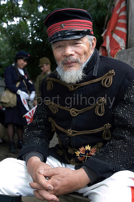 A man dressed in Edo-preriod military costume relaxes in the grounds of Yasukuni Shrine in Tokyo, Japan. very year on August 15, the day Japan officially surrendered in WWII, tens of thousands of Japanese visit the controversial shrine to pay their respects to the 2.46 million war dead enshrined there, the majority of which are soldiers and others killed in WWII and including 14 Class A convicted war criminals, such as Japan's war-time prime minister Hideki Tojo. Each year speculation escalates as to whether the country's political leaders will visit the shrine, the last to do so being Junichiro Koizumi in 2005. Nationalism in Japan is reportedly on the rise, while sentiment against the nation by countries that suffered from Japan's wartime brutality, such as China, has been further aggravated by Japan's insistence on glossing over its wartime atrocities in school text books...Photographer:Robert Gilhooly..