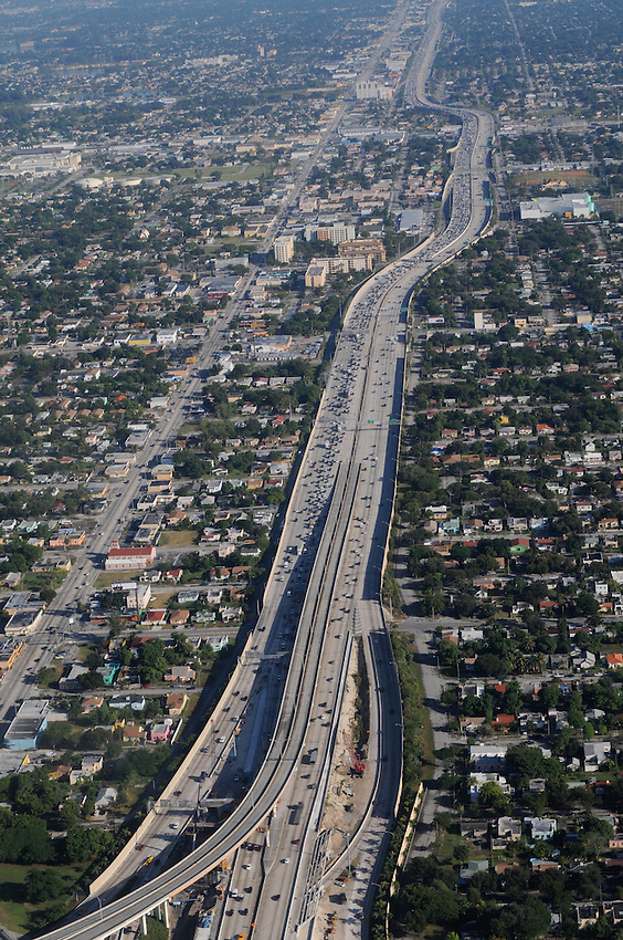 An aerial view of Miami weekday morning traffic along a freeway, seen from the vantage point of a passenger jet
