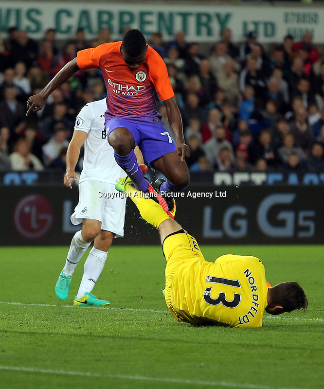 Kelechi Iheanacho of Manchester City jumps over Kristoffer Nordfeldt of Swansea City during the EFL Cup Third Round match between Swansea City and Manchester City at The Liberty Stadium in Swansea, Wales, UK. Wednesday 21 September.