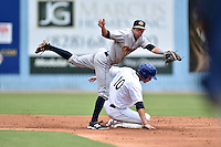 Charleston RiverDogs shortstop Tyler Wade #7 leaps over a hard sliding Jordan Patterson #10 to complete a double play during a game against the Asheville Tourists at McCormick Field July 26, 2014 in Asheville, North Carolina. The Tourists defeated the RiverDogs 9-6. (Tony Farlow/Four Seam Images)