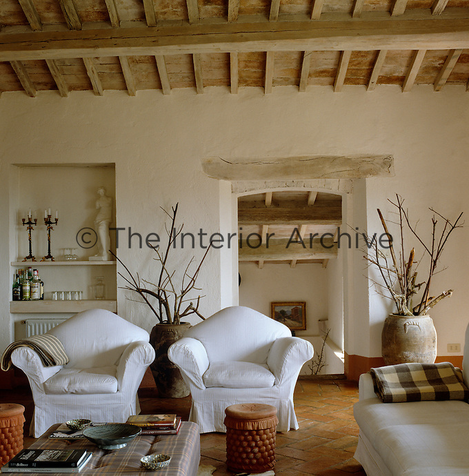 A pair of antique terracotta pots filled with branches flank the doorway of this neutrally furnished living room