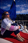 Woman enjoying sun on sailboat moored off Blake Island in Puget Sound Seattle Washington State USA.