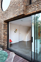 A view looking into a minimalist basement room, which has a glass sliding door leading to a decked terrace.
