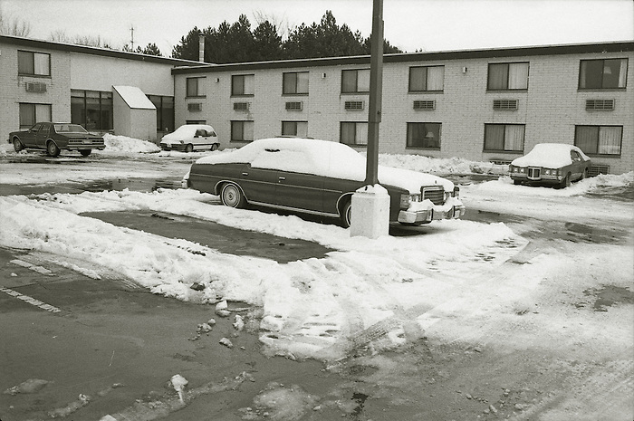 Cars parked outside a motel in North America [Niagara Falls area] covered in snow.