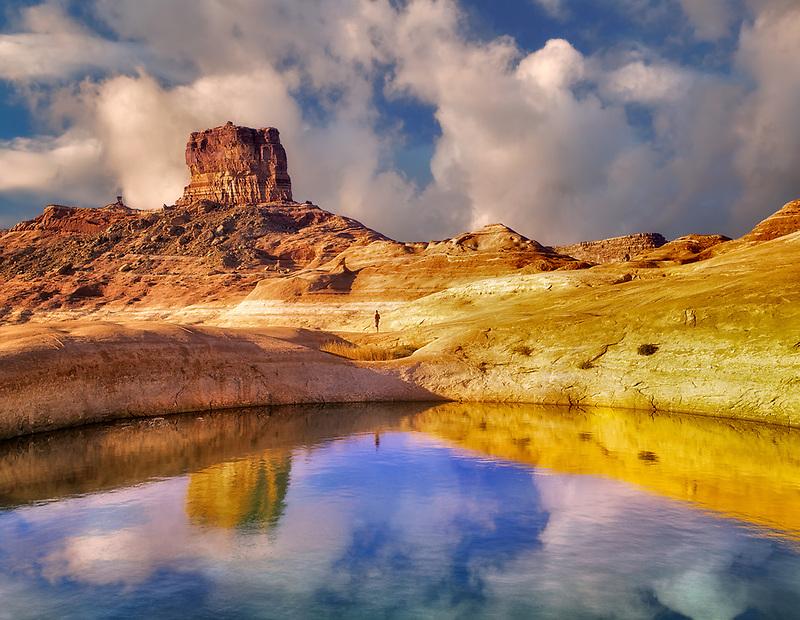 Hiker near reflection pool on banks of Lake Powell, Utah