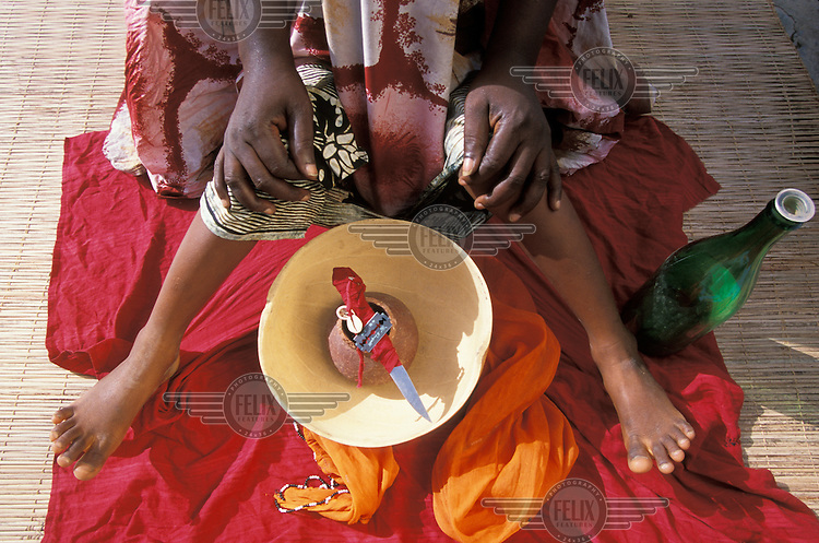 A young girl who is about to be circumcised. Her face and upper body are wrappped in a cloth, and she is restrained by the woman who will perform the circumcision, using the knife and razor blade which are in the bowl..It is estimated that about 50% of girls in Guinea Bissau undergo female genital mutilation (FGM). The figure is at least 90% in some other African countries. The practice is predominantly a cultural, rather than religious, one.