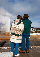 Couple watches Old Faithful Geyser erupting in winter, Yellowstone National Park, Wyoming, United States of America